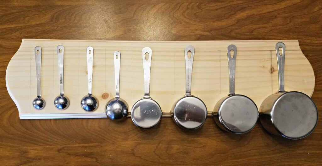 measuring spoons arranged on wood plaque with vertical pencil marks guiding where the wood burns will go