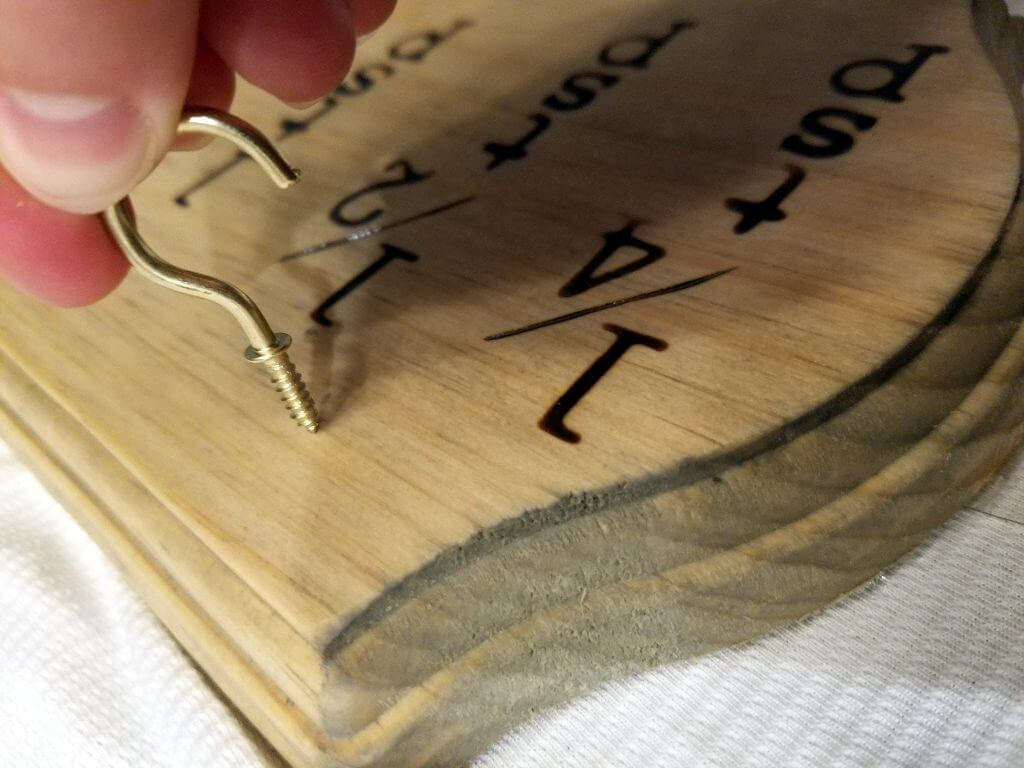 threading in mug hooks into wood plaques to hold the measuring spoons.