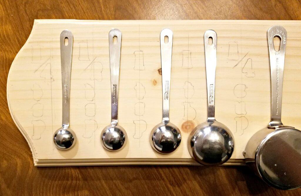 measuring spoons arranged on wood plaque and hot stamps traced along vertical lines