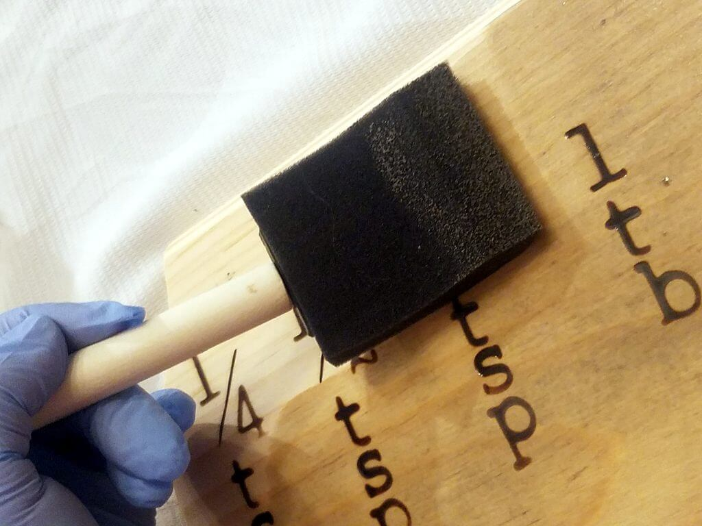 applying weathered oak stain to wood plaque with a foam brush