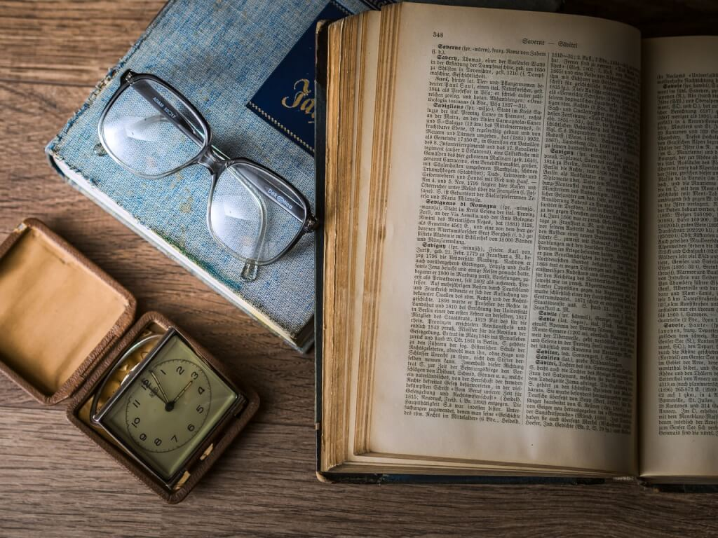 Vintage book, clock, and glasses arranged on table